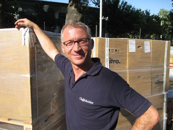 Rainer Kettner im Lagerbereich mit einem Teil der vitra Möbel